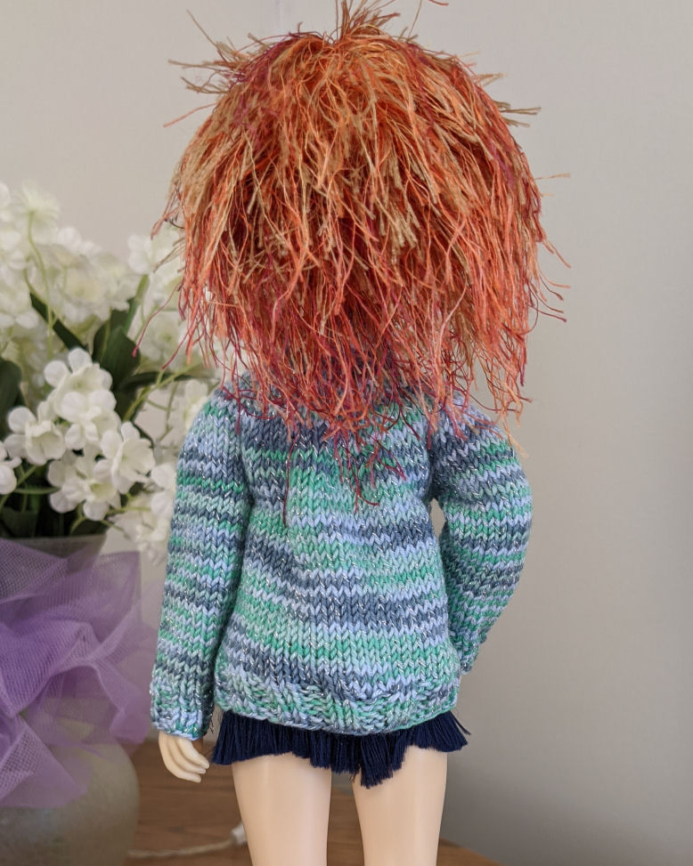 The bacl of a doll with wild orange hair wearing a sweater in shanges of blue and green. There is a bit of baggy fabric in the upper back.