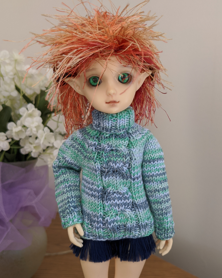 A doll with wild orange hair wearing a turtleneck sweater in shades of blue in green with a wide horseshoe cable running down the center front.